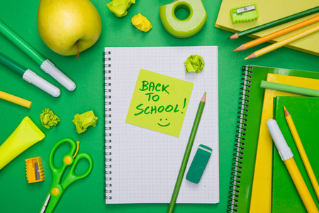 Back to school with green and yellow stationery and stick note. photo