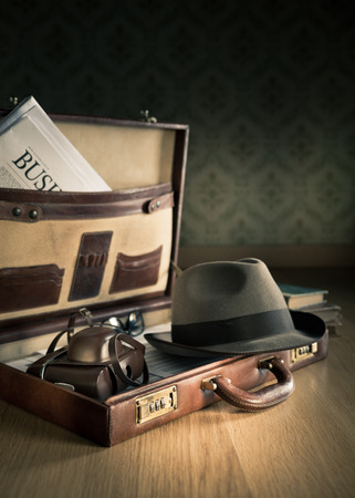 Photoreporter vintage open briefcase with old camera, newspaper and glasses. photo