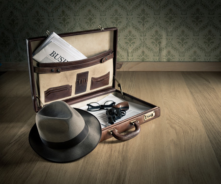 open suitcase: Open vintage leather briefcase with detective hat, revolver gun and newspaper.
