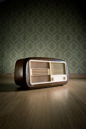 Ancienne radio vintage sur plancher de bois franc avec fond d'écran rétro sur fond. Banque d'images - 31300568