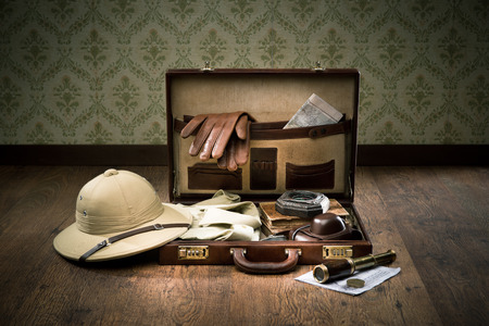 médula: Explorador de estilo colonial de embalaje con maletín de cuero abierto, sombrero médula, guantes de cuero, mapas y el telescopio de latón.