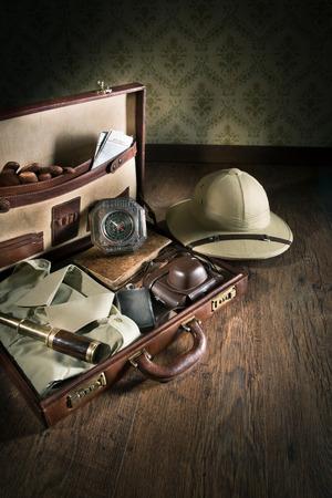 m�dula: Maleta de cuero abierta con el equipo de la vendimia aventurero, incluyendo el sombrero de la m�dula y el telescopio de lat�n. Foto de archivo