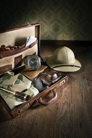 adventurer: Open leather suitcase with adventurer vintage equipment, including pith hat and brass telescope. Stock Photo