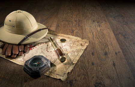 Old treasure map with colonial style pith hat, bras telescope and compass.