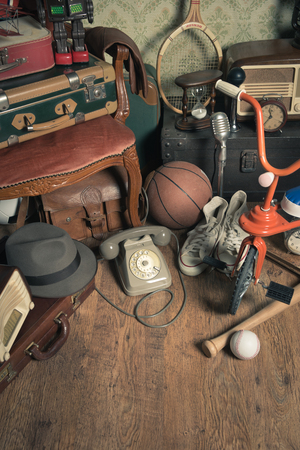 attic: Group of vintage assorted items on attic hardwood floor with vintage wallpaper background.
