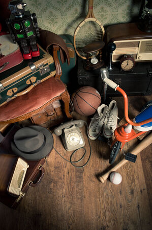 antique tricycle: Group of assorted vintage items on hardwood floor at flea market. Stock Photo