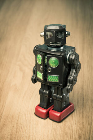 Vintage funny tin toy robot on hardwood floor looking at camera. photo