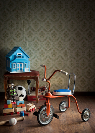 Vintage colorful tricycle with vintage toys and retro wallpaper on background. Stock Photo