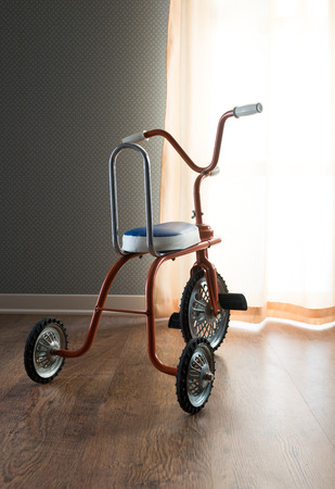 antique tricycle: Vintage colorful tricycle next to a room window with curtain. Stock Photo