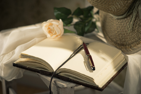 Elegant open book with pen, straw hat and white rose. photo