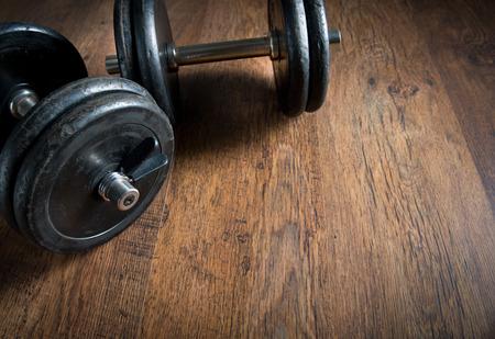 Black barbell weights on dark hardwood floor, weightlifting training concept. photo