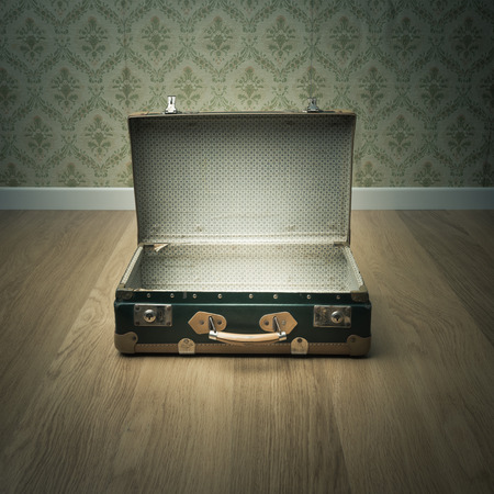 Open vintage suitcase on wooden floor with vintage wallpaper on background. photo