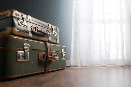 packing suitcase: Pile of vintage suitcases next to a window on hardwood floor.