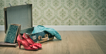 red shoes: Elegant vintage open suitcase with female red shoes, dotted clothing and books.