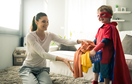 Superhero boy and his mother doing laundry together in the living room. photo