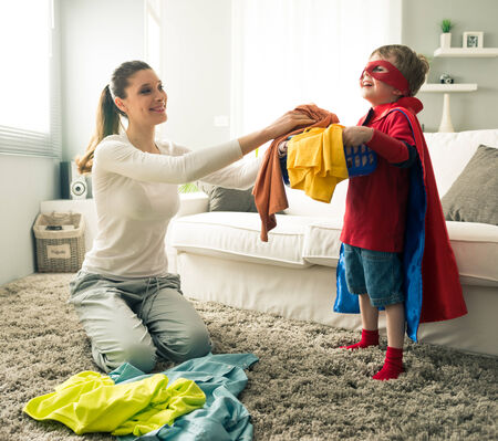 doing laundry: Superhero boy and his mother doing laundry together in the living room.
