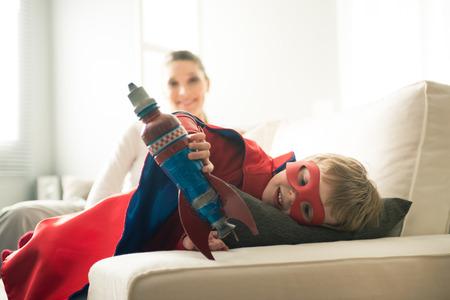 infant: Muchacho lindo del super h�roe con el pago de cohete de juguete en la sala de estar con su madre en el fondo.