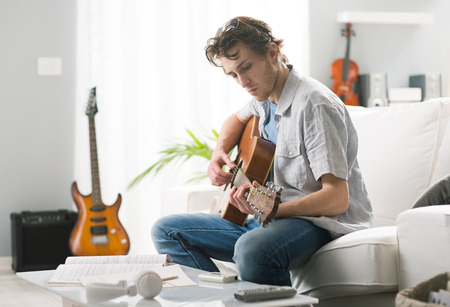 Young man playing guitar and composing a song sitting on sofa. Archivio Fotografico