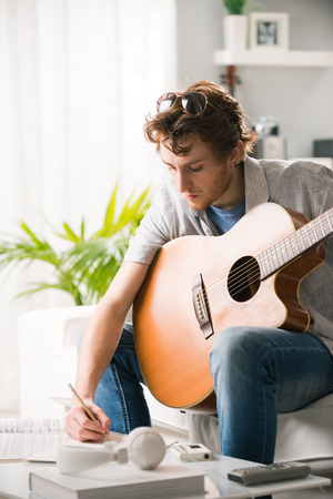 young man: Young man playing guitar and composing a song sitting on sofa. Stock Photo