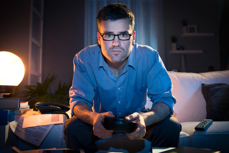 gamepad: Man playing videogames late at night in a messy living room, sitting on sofa.