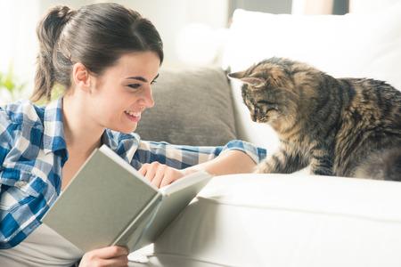 gato jugando: Sonriente mujer jugando con su gato y con un libro en la sala de estar.