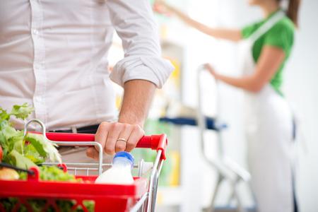 carro supermercado: La mano de cerca Supermercado del cliente con el empleado de ventas en el fondo. Foto de archivo