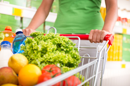 spending full: Woman in green t-shirt pushing a shopping cart at store with shelves on background. Stock Photo