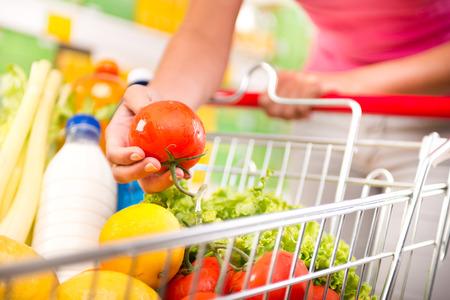 Carrinho de compras cheio na loja com legumes frescos e mãos close-up.