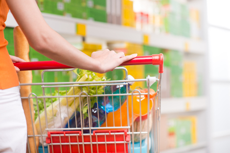 spending full: Woman shopping at supermarket, hands on trolley close-up.
