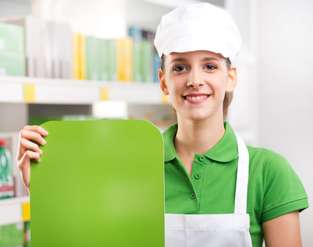 Female sales clerk holding a green sign and smiling with supermarket shelf on background. photo