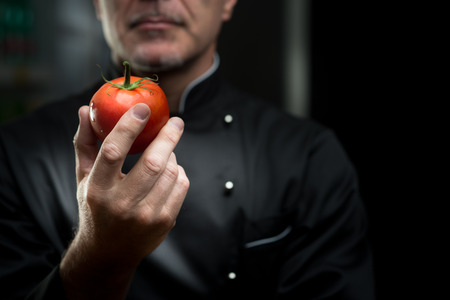 Confident elegant chef holding a delicious tomato on dark background.