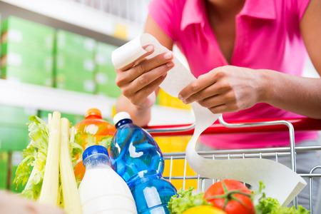 carro supermercado: Mujer irreconocible comprobar un recibo de comestibles largo inclinado a un carrito de la compra lleno en la tienda.