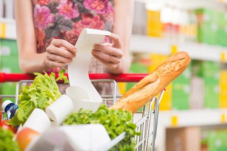 carro supermercado: Mujer irreconocible comprobar un recibo de supermercado de largo con comestibles sobre los conocimientos adquiridos. Foto de archivo