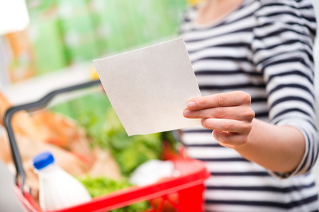 shopping list: Woman at supermarket holding a full shopping basket and a shopping list.