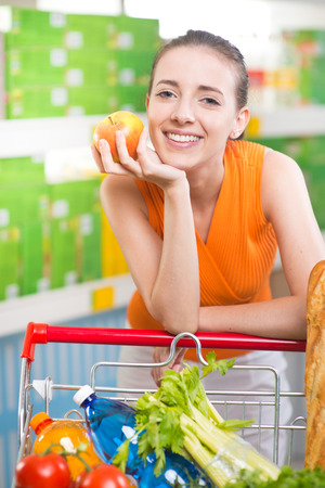 Attractive young woman holding an apple and smiling at supermarket. photo