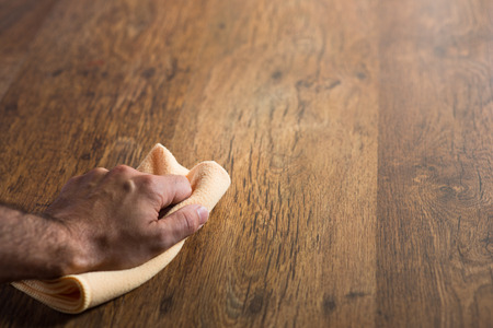 rinsing: Male hand cleaning and rubbing an hardwood floor with a microfiber cloth. Stock Photo