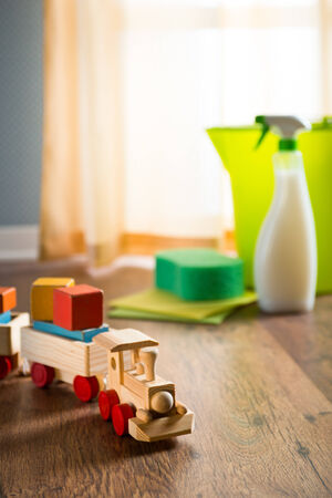 safe house: Wooden toy train with cleaning products on background next to a window. Stock Photo