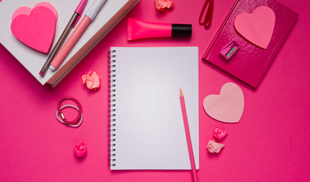 Girly pink desktop and stationery with blank notebook and pencil.
