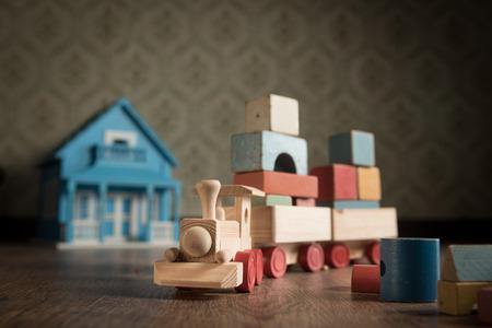 juguetes antiguos: Tren de madera y casa de muñecas en el suelo con el papel pintado de la vendimia en el fondo.