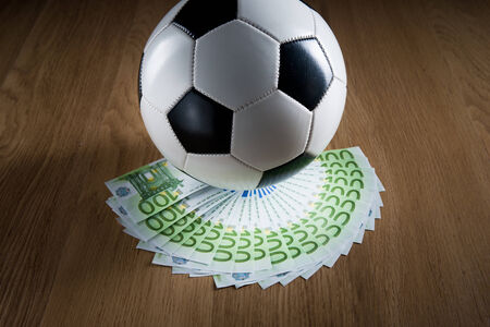 Soccer ball with fan of euro banknotes on hardwood floor. photo