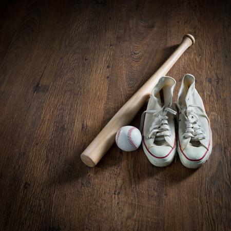 hardball: Baseball equipment on hardwood floor including canvas shoes, hardball and bat. Stock Photo