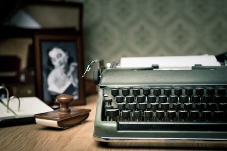 Vintage typewriter on a wooden desk with old frame and picture on background. Imagens