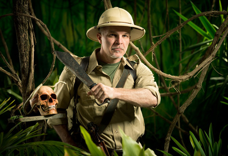 Adventurer with colonial style survival equipment in the jungle with skull. photo