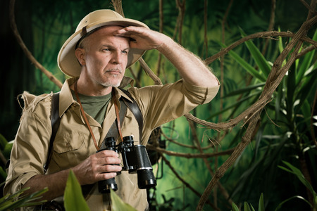 Expert explorer in the forest looking away and holding binoculars.