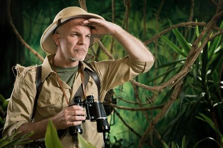 Explorateur d'experts dans la forêt en regardant ailleurs et tenant des jumelles.