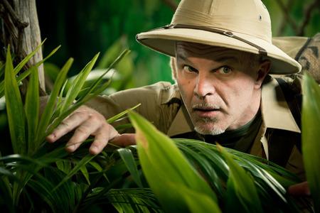 médula: Aventurero ocultando y mirando a través de las plantas en la selva selva tropical con equipos de exploración.