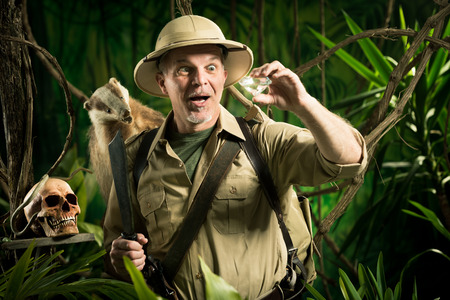 Smiling adventurer finding a huge diamond in the jungle with explorer equipment. photo