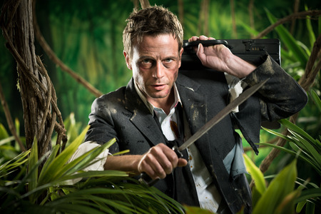 Confident strong businessman dealing with jungle dangers, holding a machete.