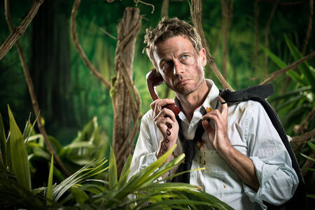business survival: Depressed businessman in torn clothing lost in jungle having a phone call.