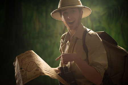 Young explorer in the jungle finding the right direction and holding an old map. photo